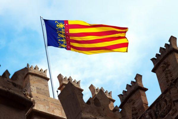 Valencia flag at top of Lonja de la Seda. Valencia, Spain